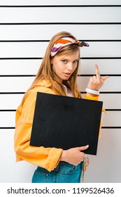 arrested hipster girl posing with empty prison board and showing middle finger in front of police line up