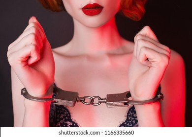Arrested redhead girl with handcuffs on black background. Sexual bdsm toy. Woman submission. Outfit for playing bdsm games. Arrested lady with metal handcuffs on hands. Submission in society