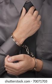 Arrested white man in handcuffs straightens his tie.