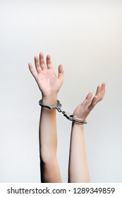 Arrested woman handcuffed hands. Prisoner or arrested terrorist, close-up of hands in handcuffs isolated on brown background. Criminal female hands locked in handcuffs. Close-up view.