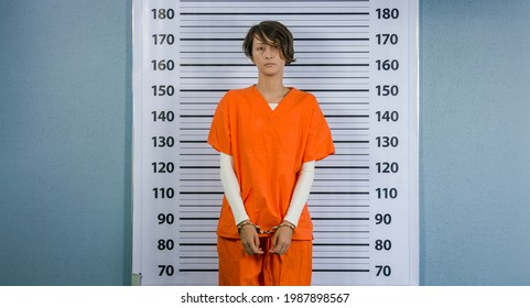 Arrested woman posing in an orange suit for a mugshot