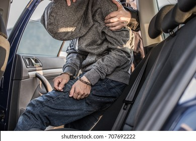 Arresting a thief, a criminal, a drug dealer with hands armed with police cuffs, a thief disabled, Two policemen lead him and lead him to the car