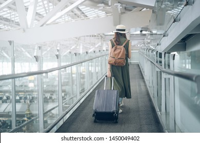 arrival on broad Asian woman traveler walking dragging luggage to travel to the airport in time to board the plane