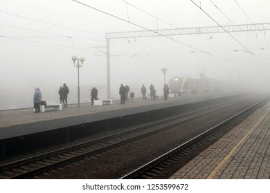 The arrival of the train in the fog on the platform with passengers