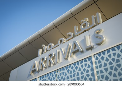 Arrivals sign at an airport in the Middle East features Arabic text and Islamic patterns under modern architecture and bright blue sky