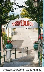 Arrivederci or Goodbye sign in Italian over the gate in rural Switzerland