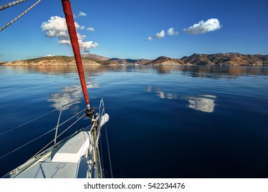 Arriving to Amorgos island with a sailing boat on a calm sea with reflecting clouds, Greece