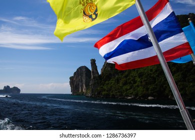 Arriving on tropical island Ko Phi Phi with ferry from Phuket - Close up of Thai flag waving from the boat with rocky coast line, Thailand