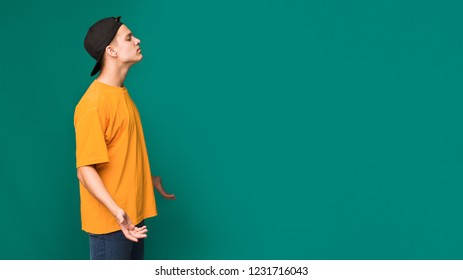 Arrogant and cocky guy looking at copy space with question, turquoise background