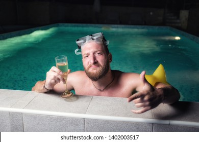 Arrogant cocky young caucasian man toasting to the good life while standing in a pool at night, wearing swimming goggles, holding champagne glass in one hand and showing shaka sign with the other hand