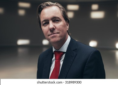 Arrogant entrepreneur wearing suit with red tie in empty room.