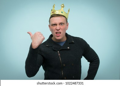 Arrogant  man with golden crown above his head is yelling isolated on blue background. Wicked and arrogant boss. Person with a high self-esteem.