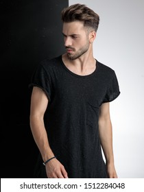 arrogant young man wearing black t-shirt, looking to side and standing on black and white background in studio