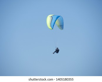Arromanches, France, 21may 2019: Paragliding in the sky. Paraglider tandem flying over the sea with blue water and mountains in bright sunny day. Extreme sport. Landscape - Image