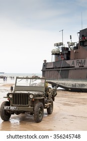 ARROMANCHES, FRANCE - JUNE 06, 2009: Willies jeep and landing craft on Gold beach during the 65th Anniversary of D-Day