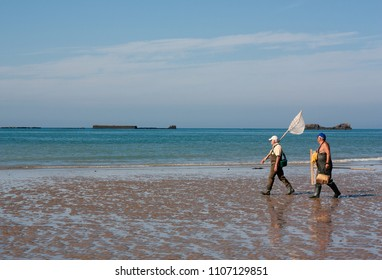 ARROMANCHES-LES-BAINS,NORMANDY-CIRCA JULY 2017: Fishermen walking on the beach  beach during the low tide on the seaside town of Arromanches on July 2017