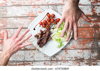 Arrosticini meat in a dish with salad and tomatoes on the table