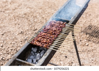 The arrosticini, a typical food from the Abruzzo region (Italy). Small skewers of sheep meat that are cooking on the grill