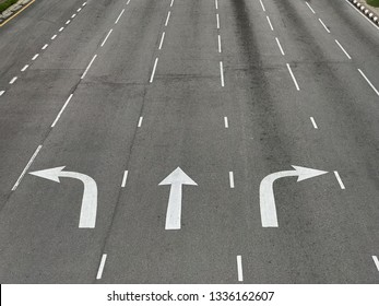 Arrow directions on asphalt road at a junction.