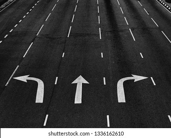 Arrow directions on asphalt road at a junction in black and white (monochrome).