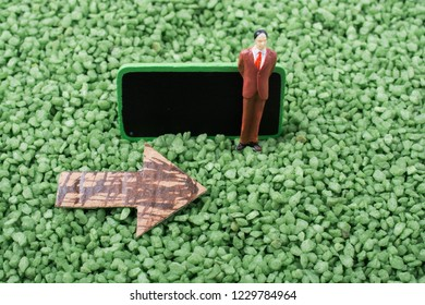 Arrow and man figurine of notice board on sand