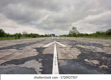 Arrow marking on an abandoned airport runway on a grey cloudy day.