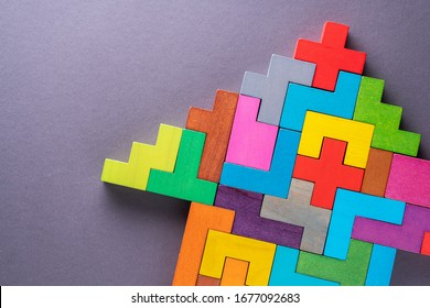 Arrow of multi-colored wooden shapes on gray background with copy space.
