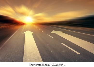 arrow on the road with sunset sunrise on horizon