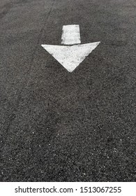 Arrow painted on street with white paint asphalt for directions and safety driving on road
