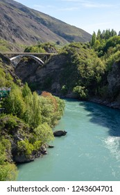 Arrow River at Arrowtown, South Island, New Zealand, with rocky, bushy banks and teal water.