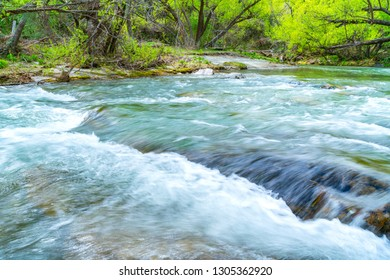 Arrow River flowing fast through gorge lined with lush green deciduous trees