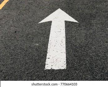 Arrow road sign on the asphalt