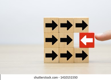 The arrow shows the direction on the wooden block for Stand out think different,Leadership,Courage,Change to success concept.