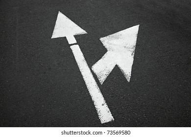 Arrow sign on an asphalt surface