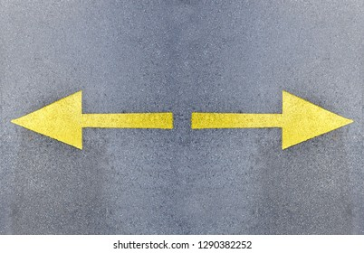 Arrow signs on asphalt road showing direction of movement, close up right and left