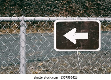Arrow symbol direction sign on chain link fence.