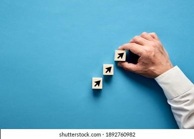 Pfeilsymbol auf Holzblöcken mit Hand eines Geschäftsmanns, der die Blöcke anordnet. Konzept des wirtschaftlichen, finanziellen oder wirtschaftlichen Wachstums.
