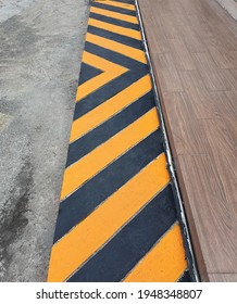 Arrow-like Yellow and black lines or yellow lines on curb or pedestrian lines are