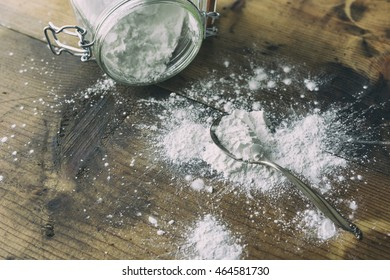 Arrowroot powder in a silver spoon. Shown on wooden table with a spilled jar.  Low key image.