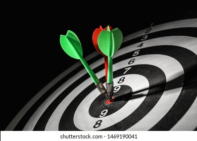 Arrows hitting target on dart board against black background
