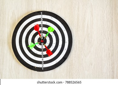 Arrows on target dart on wooden background. Top view.