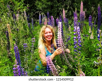 Arrowtown / New Zealand - 12 21 2016: happy smiling blond girl amazed by blossoming lupine flowers (Lupinus perennis) in the green lush meadow