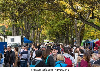 Arrowtown, New Zealand- April 23, 2016: People are walkin along the historic tree walk and talking to each other at the Arrowtown Autumn Festival. Background are some trees and historic buildings.