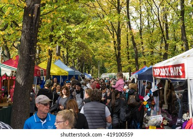 Arrowtown, New Zealand- April 23, 2016: People are walkin along the historic tree walk and shopping from Art and Craft market at the Arrowtown Autumn Festival. In the background are some trees.
