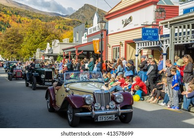 Arrowtown, New Zealand - April 23,2016 : There is a vintage cars parade event during the Arrowtown Autumn Festival on Buckingham Street, people can seen watching and enjoying the parade.