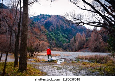 Arrowtown, New Zealand - August 2018: A lone hiker stands by a stream, admiring the beautiful view. Colourful river valley with a backdrop of forested mountains