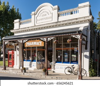 Arrowtown, New Zealand - March 16, 2017: The white painted old building of the active pharmacy in town. Bike and red phone booth in shot. Posters in window.