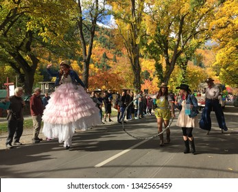 Arrowtown/NewZealand 28 Mar 2018: Arrowtown Autumn festival Parade Man and woman walking on stilt wearing pink many layers Elizabeth era dress and costume blue trousers grey vest yellow leaves