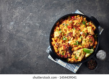 Arroz con pollo, spanish cuisine, rice with chicken and vegetables in a saucepan on a concrete table, view from above, flatlay, copy space