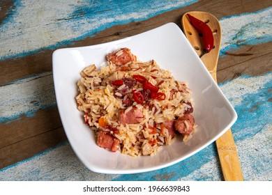 Arroz de Carreteiro - Typische Lebensmittel aus Südbrasilien, hergestellt mit Reis, getrocknetem Fleisch, Pfefferoni-Wurst, Schweinelende und Speck auf rustikalem bunten Holztisch